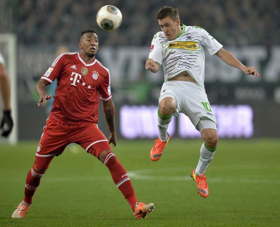 Photo - Moenchengladbach's Max Kruse, right, and Bayern's Jerome Boateng challenge for the ball during the German Bundesliga soccer match between Borussia Moenchengladbach and Bayern Munich in Moenchengladbach,  Germany, Friday, Jan. 24, 2014. (AP Photo/Martin Meissner)
