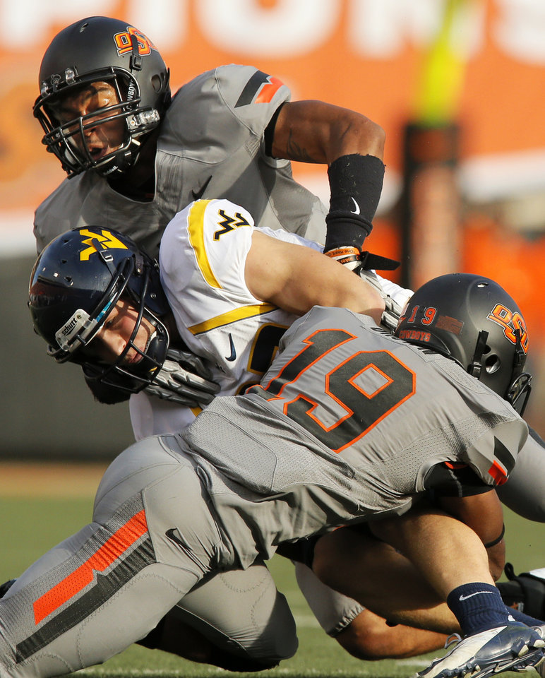 Photo - Oklahoma State's Lyndell Johnson (27), back, and Brodrick Brown (19) stop West Virginia's Connor Arlia (83) during a college football game between Oklahoma State University (OSU) and West Virginia University (WVU) at Boone Pickens Stadium in Stillwater, Okla., Saturday, Nov. 10, 2012. Photo by Nate Billings, The Oklahoman