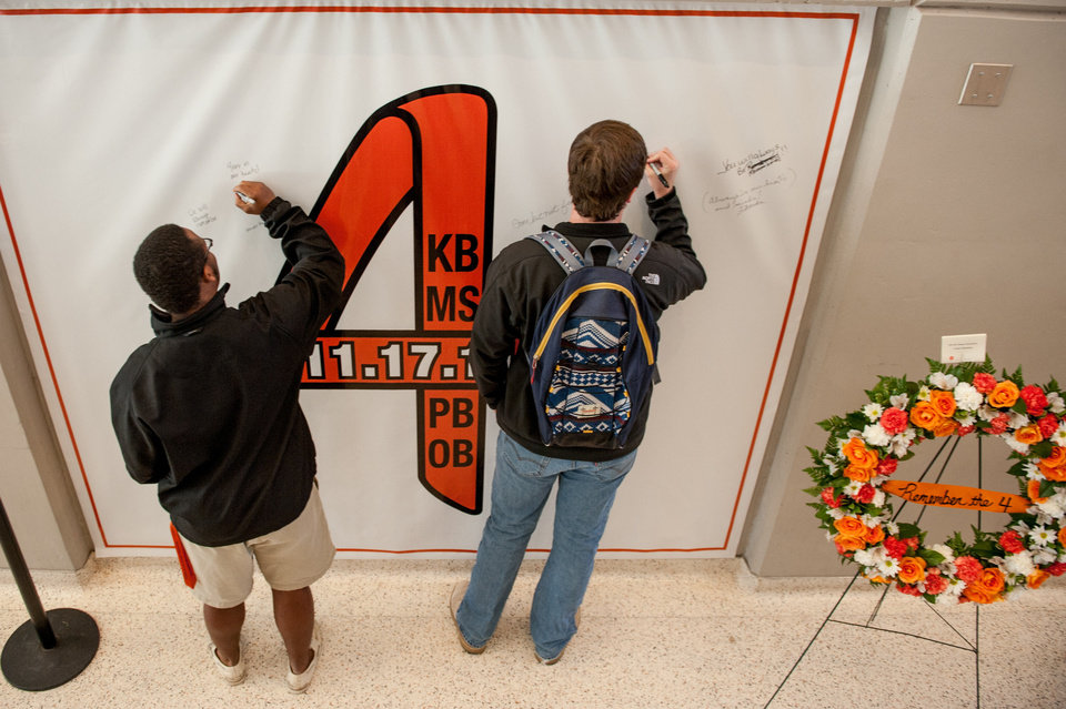 "Tre Bailey, left, and Rowan Davis write on the ""Remember the 4"" banner Friday in Gallagher-Iba Arena in Stillwater. Saturday marks one year since a plane crash that killed two Oklahoma State University women's basketball coaches and two OSU supporters. Photo by Mitchell Alcala, for The Okahoman"