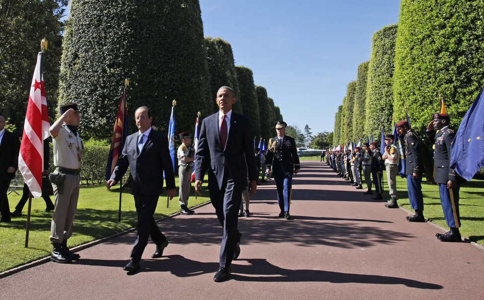 Photo - U.S. President Barack Obama, foreground centre, and French President Francois Hollande arrive at Normandy American Cemetery at Omaha Beach as he participates in the 70th anniversary of D-Day, in Colleville sur Mer in Normandy, France, Friday, June 6, 2014. (AP Photo/Charles Dharapak)