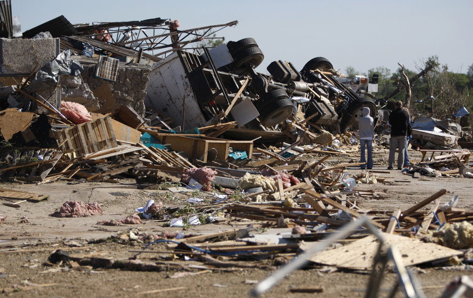 Photo - People stand by the remains of a business in Woodward, Okla., Sunday, April 15, 2012. A tornado that killed five people struck Woodward, Okla., shortly after midnight on Sunday, April15, 2012.  Photo by Bryan Terry, The Oklahoman
