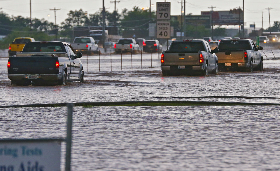Photo - Trucks try to drive through the flooded portion of the I-35  access road in Moore, Okla. on Wednesday, May 6, 2015.  Photo by Chris Landsberger, The Oklahoman