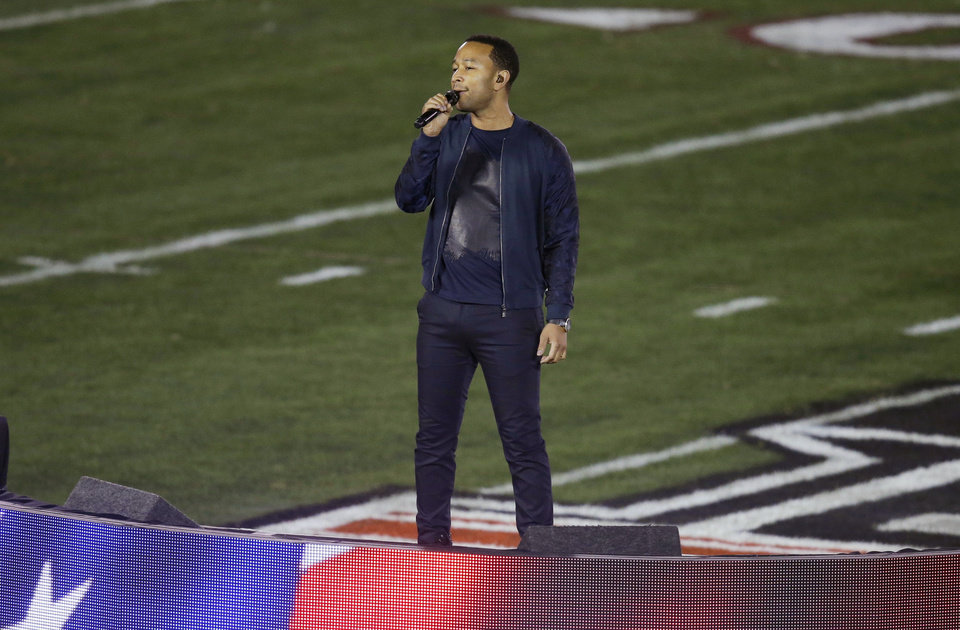 Photo - FILE - This Jan. 6, 2014 file photo shows John Legend singing the national anthem before the NCAA BCS National Championship college football game between Auburn and Florida State in Pasadena, Calif. Legend will perform at exclusive engagements and will make appearances during Super Bowl XLV111 weekend. (AP Photo/Gregory Bull, File)