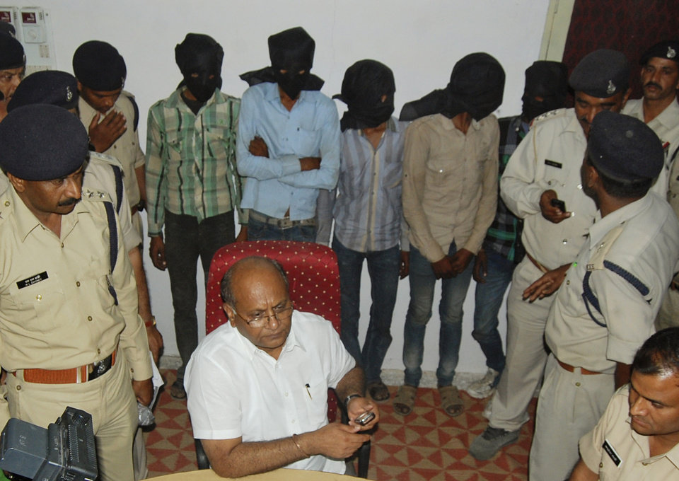 In this Sunday, March 17, 2013 photo, five men, faces covered, who are among the six accused of raping a Swiss tourist who was cycling with her husband in central India, stand at a police control room after they were detained, in Datia, India. The attack occurred Friday night as the Swiss couple camped in a forest in Datia district. (AP Photo)