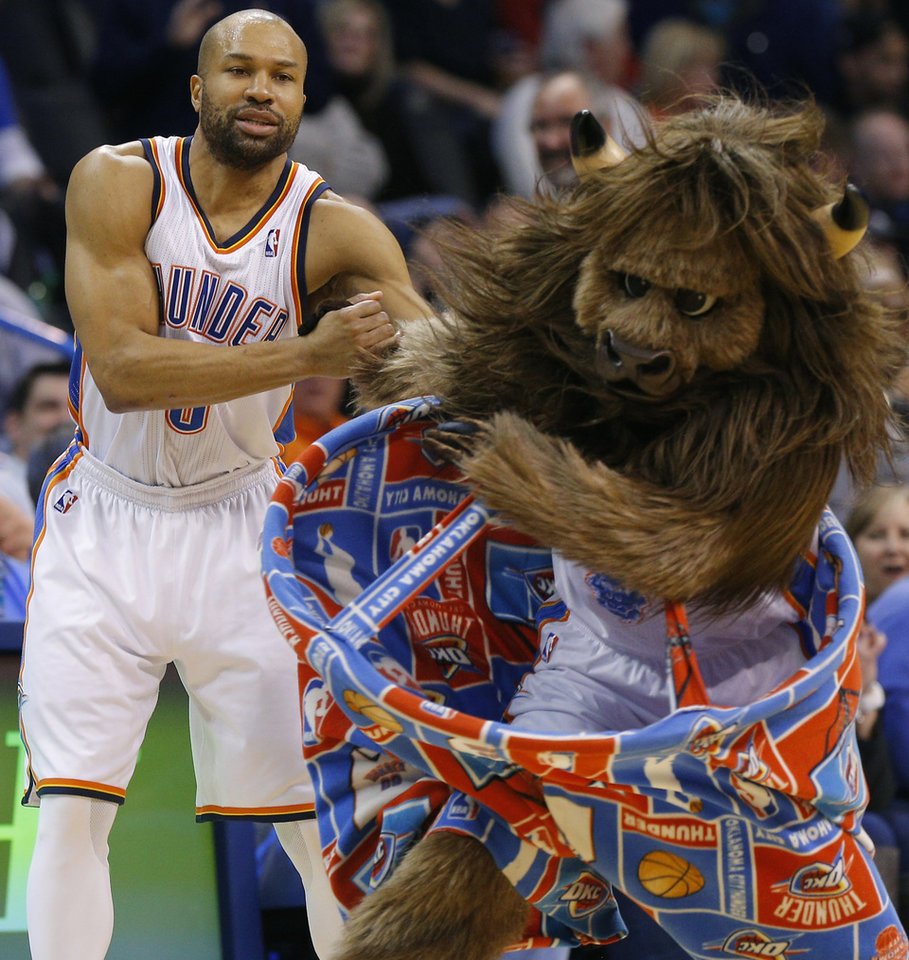 Photo - Oklahoma City's Derek Fisher (6) helps Rumble the Bison up during an NBA basketball game between the Oklahoma City Thunder and the Philadelphia 76ers at Chesapeake Energy Arena in Oklahoma City, Tuesday, March 4, 2014. Oklahoma City won 125-92.  Photo by Bryan Terry, The Oklahoman