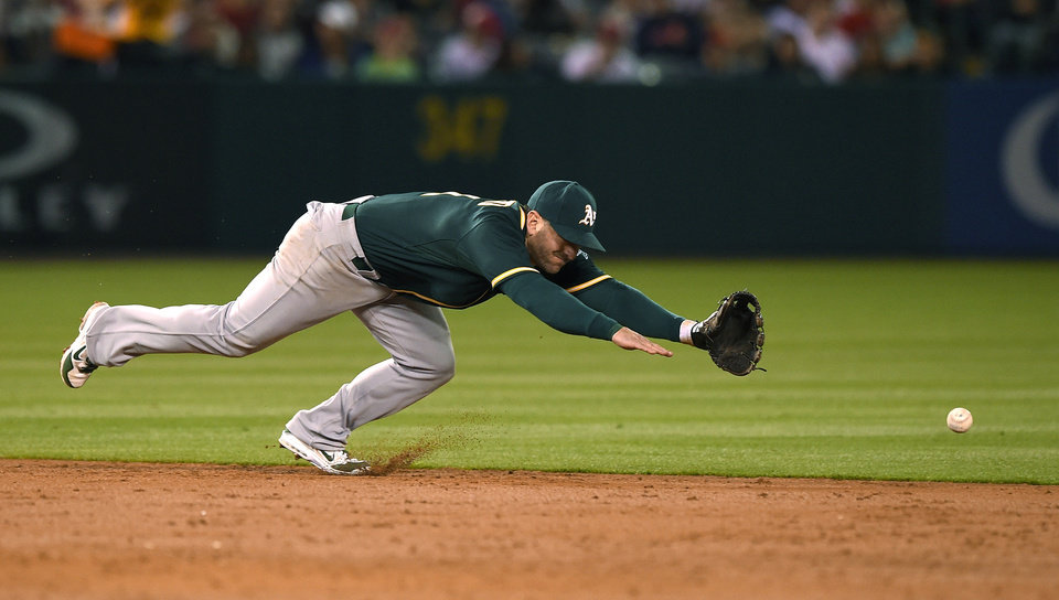 Photo - Oakland Athletics shortstop Nick Punto can't reach a ball hit for a single by Los Angeles Angels' Erick Aybar during the third inning of a baseball game, Wednesday, April 16, 2014, in Anaheim, Calif. (AP Photo/Mark J. Terrill)
