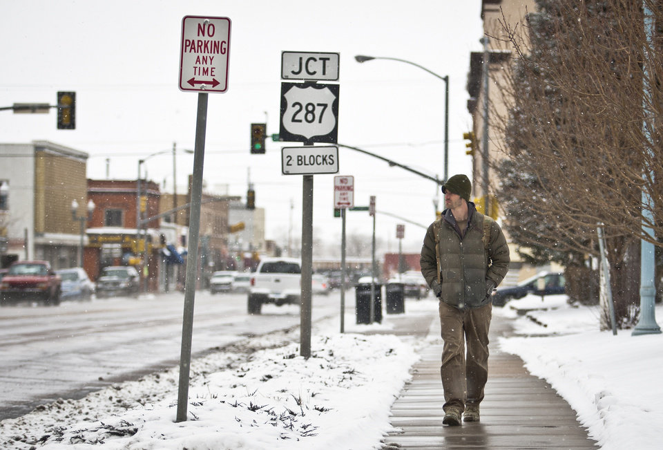 Photo - Laramie resident Leeds Butler walks down the sidewalk along Grand Avenue during an early afternoon snowfall in Laramie, Wyo., Tuesday, April 9, 2013. (AP Photo/Laramie Boomerang, Jeremy Martin)