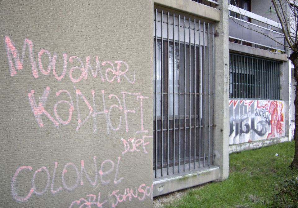 Photo - This photo taken Feb. 7, 2013, shows graffiti on a building in Montfermeil, outside Paris, which reads