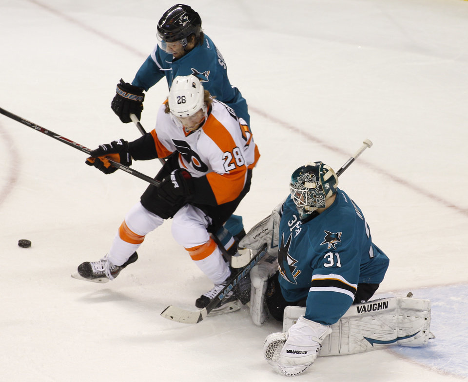 Photo - Philadelphia Flyers' Claude Giroux (28) and San Jose Sharks' Brad Stuart struggle for the puck in front of Sharks goalie Antti Niemi (31) during the second period of an NHL hockey game, Monday, Feb. 3, 2014, in San Jose, Calif. (AP Photo/George Nikitin)