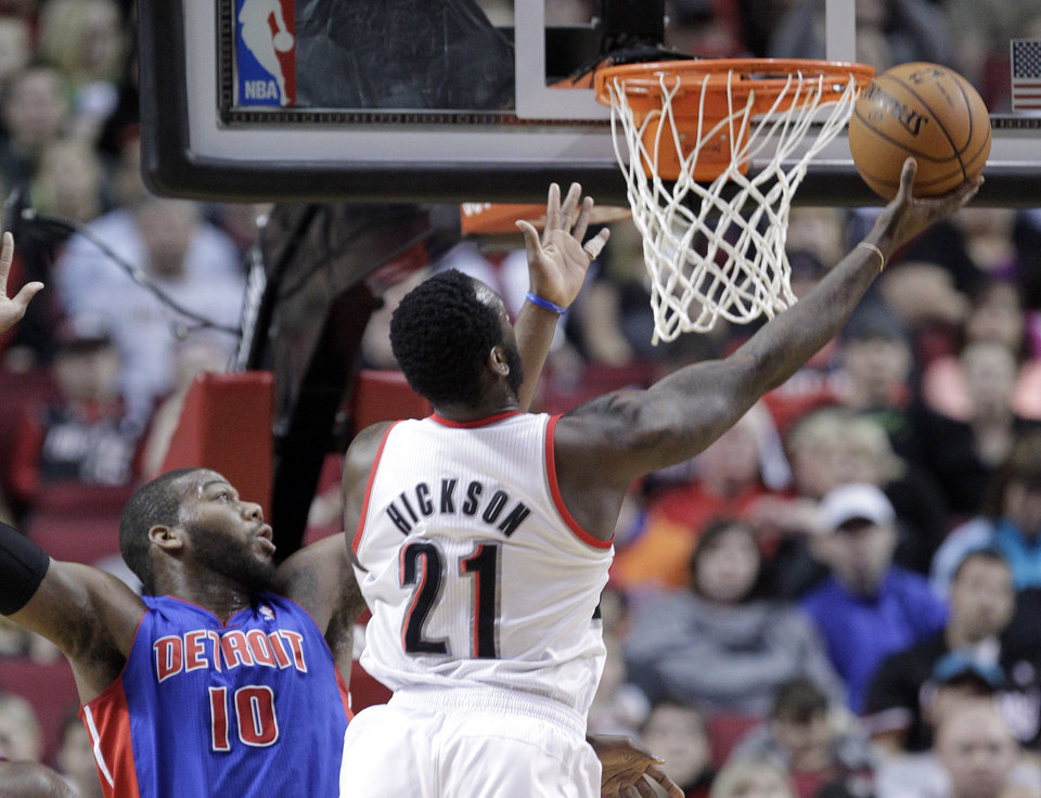 Portland Trail Blazers center J.J. Hickson (21) goes to the basket past Detroit Pistons center Greg Monroe during the first quarter of an NBA basketball game in Portland, Ore., Saturday, March 16, 2013. (AP Photo/Don Ryan)