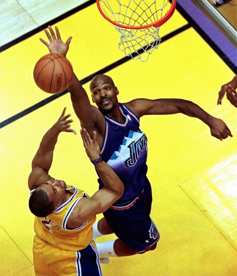 Photo - Utah Jazz basketball player Bryon Russell, right, attempts to block a shot by Los Angeles Lakers player Derek Fisher during the first half of Game 4 of the Western Conference finals, Sunday, May 24, 1998, in Inglewood, Calif. The Jazz beat the Lakers, 94-92, to advance to the NBA finals. (AP Photo/Mark J. Terrill)