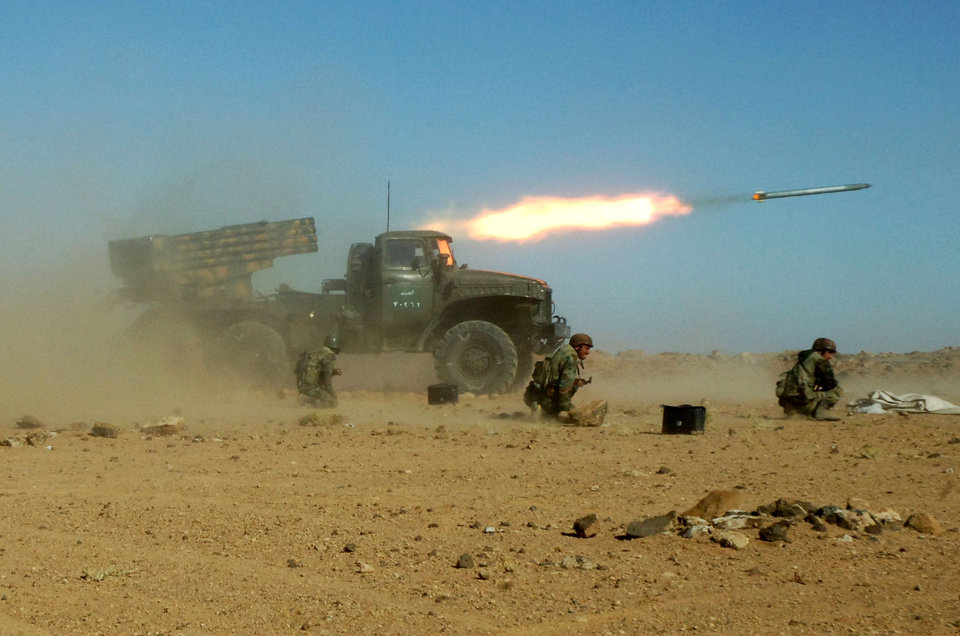 Photo - HOLD FOR STORY SYRIA ASSAD'S OPTIONS BY RYAN LUCAS - FILE - This Sunday, Dec. 4, 2011 photo provided by the Syrian official news agency SANA, shows Syrian soldiers kneeling next to a multiple rocket launcher as they fire missiles during a maneuver at an unknown location, in Syria. As the Obama administration tries to prod Congress into backing armed action against Syria, the regime in Damascus is hiding military hardware and shifting troops out of bases into civilian areas. (AP Photo/SANA, File)