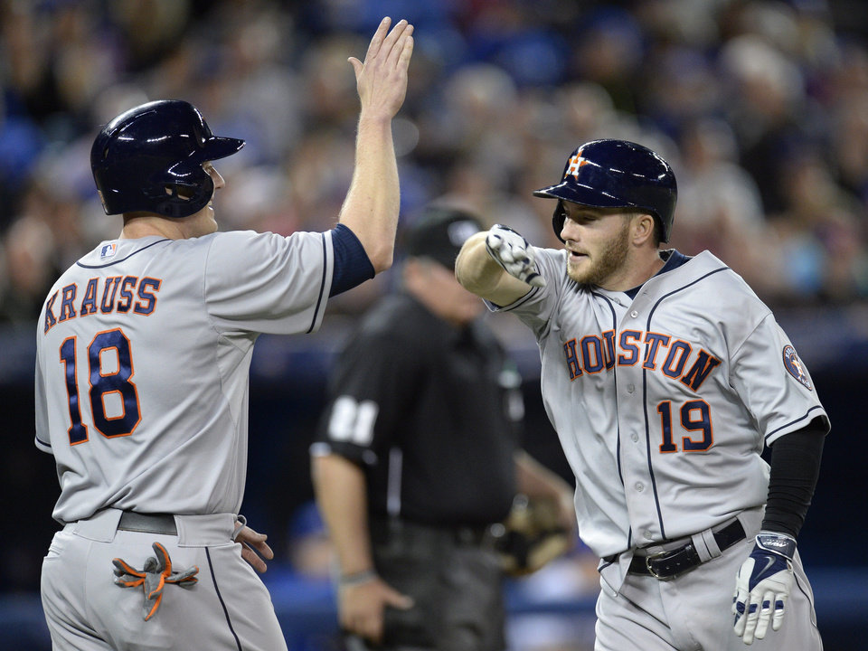 Photo - Houston Astros' Robbie Grossman celebrates his two-run home run off Toronto Blue Jays pitcher R.A. Dickey with teammate Marc Krauss during the fifth inning of baseball game in Toronto on Thursday, April 10, 2014. (AP Photo/The Canadian Press, Frank Gunn)