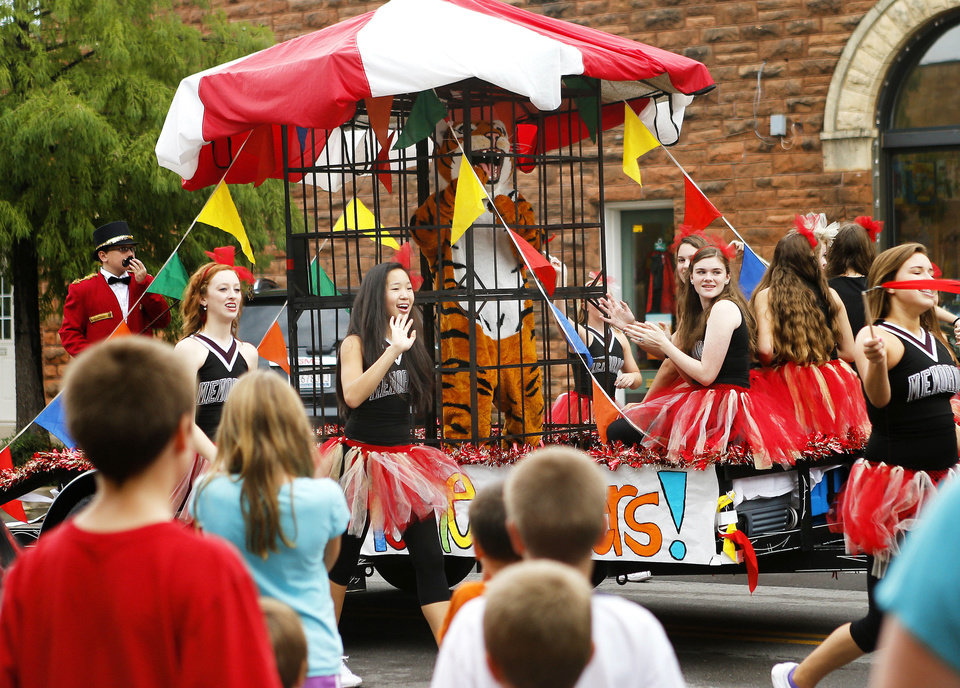 Photo - Left: A crowd watches the  Edmond Memorial junior varsity pom float pass by during the homecoming parade.  Photos by Bryan Terry, The Oklahoman