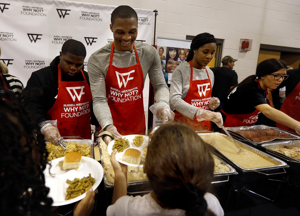 Photo - Russell Westbrook serves Thanksgiving dinner at the Boys & Girls Club of Oklahoma County in Oklahoma City, Thursday, Nov. 20, 2014. The Russell Westbrook Why Not Foundation and the The Oklahoma City Association of Professional hosted the dinner. Photo by Sarah Phipps, The Oklahoman