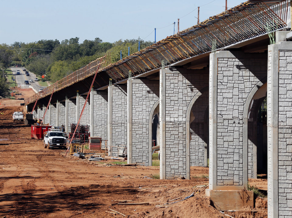 Photo -  Workers build a new bridge with ornate columns for State Highway 33 over Cottonwood Creek on Monday in Guthrie. [Photo by Steve Sisney, The Oklahoman]