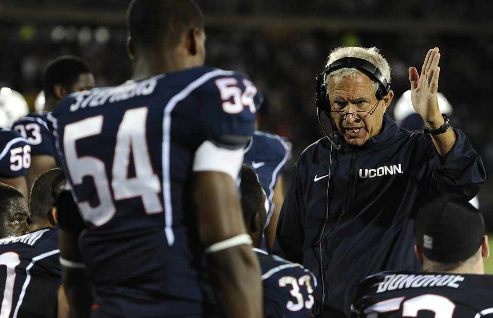 Photo - Connecticut head coach Paul Pasqualoni, right, gestures to his team during the second half of an NCAA college football game against Michigan at Rentschler Field, Saturday, Sept. 21, 2013, in East Hartford, Conn. (AP Photo/Jessica Hill)