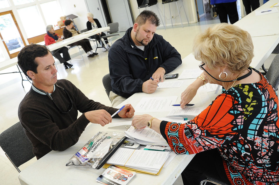 Voters Will Murray, left, and Brian Ross fill out affidavit ballots with help from Precinct Manager Margaret Brown on Tuesday, Nov. 6, 2012, at St. Philip\'s Episcopal Church in Jackson, Miss. (AP Photo/The Clarion-Ledger, Joe Ellis) NO SALES.