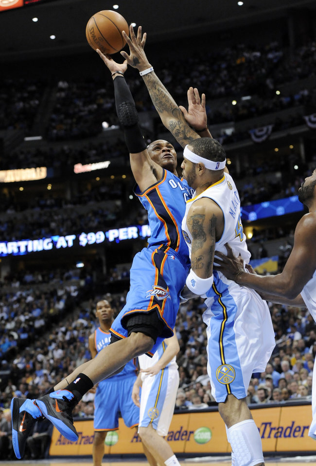 Photo - Oklahoma City Thunder guard Russell Westbrook (0) goes up for a shot against Denver Nuggets forward Kenyon Martin (4) during the first half in game 4 of a first-round NBA basketball playoff series Monday, April 25, 2011, in Denver. (AP Photo/Jack Dempsey)