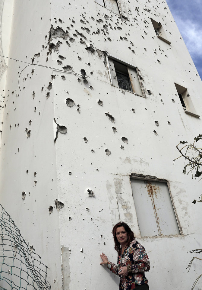 A woman stands next to a damaged house after a rocket fired by Palestinian militants from Gaza Strip landed in Ashkelon, southern Israel, Sunday, Nov. 18, 2012. Israel launched the operation last Wednesday by assassinating Hamas' military chief and carrying out dozens of airstrikes on rocket launchers and weapons storage sites. Over the weekend, the operation began to target Hamas government installations as well, including the offices of its prime minister and attacks on a major training base and the two media centers. (AP Photo/Tsafrir Abayov)