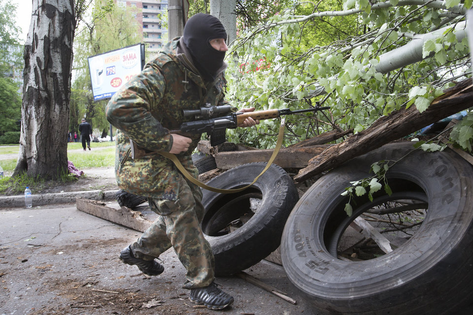 Photo - A Pro-Russian gunman runs behind barricades holding a weapon in Slovyansk, eastern Ukraine, Friday, May 2, 2014. Ukraine launched what appeared to be its first major assault against pro-Russian forces who have seized government buildings in the country's east, with fighting breaking out Friday in a city that has become the focus of the insurgency. (AP Photo/Alexander Zemlianichenko)