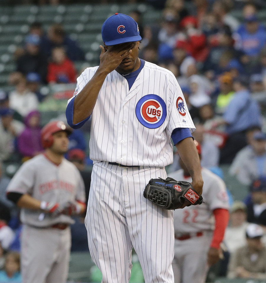 Photo - Chicago Cubs starter Edwin Jackson wipes his face after Cincinnati Reds' Joey Votto walked to first base during the first inning of a baseball game in Chicago, Wednesday, June 25, 2014. (AP Photo/Nam Y. Huh)