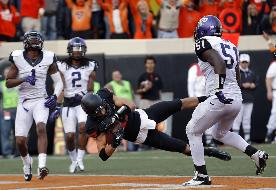 Photo - Oklahoma State's Charlie Moore (17) dives for a touchdown as TCU's Chris Hackett (1), Jason Verrett (2) and Kenny Cain (51) look on during a college football game between Oklahoma State University (OSU) and Texas Christian University (TCU) at Boone Pickens Stadium in Stillwater, Okla., Saturday, Oct. 27, 2012. Photo by Sarah Phipps, The Oklahoman