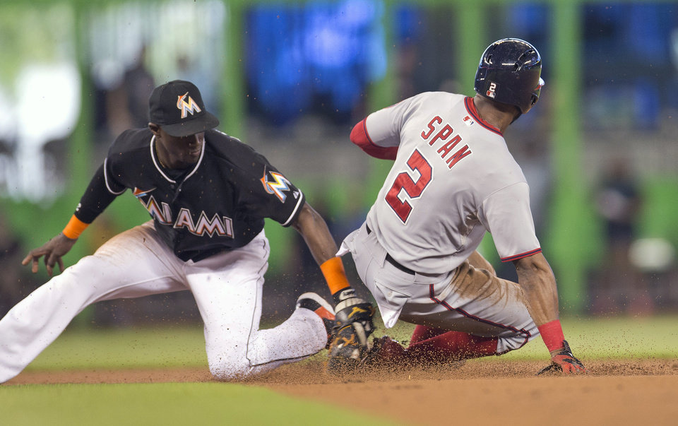 Photo - Washington Nationals runner Denard Span (2) steals second on a late throw to Miami Marlins short stop Adeiny Hechavarria (3) during the first inning of a baseball game in Miami, Wednesday, July 30, 2014. (AP Photo/J Pat Carter)