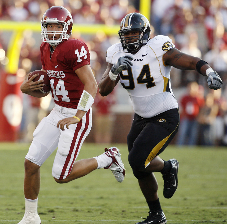 Photo - Oklahoma's Sam Bradford (14) out runs Missouri's Evander Hood (94) during the first half of the college football game between the University of Oklahoma Sooners (OU) and the University of Missouri Tigers (MU) at the Gaylord Family Oklahoma Memorial Stadium on Saturday, Oct. 13, 2007, in Norman, Okla.By STEVE SISNEY, The Oklahoman