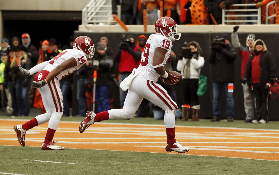 Photo - Oklahoma's Eric Striker (19) scores in front of Aaron Colvin (14) on fumble recovery on the final play of the Bedlam college football game between the Oklahoma State University Cowboys (OSU) and the University of Oklahoma Sooners (OU) at Boone Pickens Stadium in Stillwater, Okla., Saturday, Dec. 7, 2013. OU won, 33-24. Photo by Nate Billings, The Oklahoman