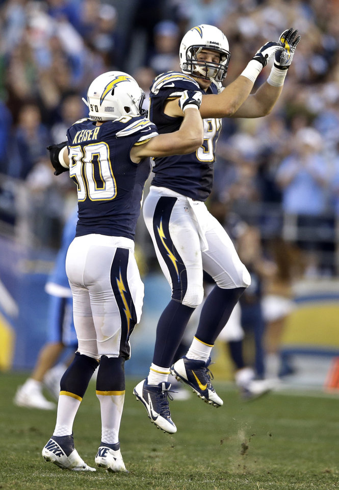 Photo - San Diego Chargers outside linebacker Thomas Keiser, left, and inside linebacker Bront Bird celebrate after the Chargers' 27-24 victory over the Kansas City Chiefs in an overtime NFL football game, Sunday, Dec. 29, 2013, in San Diego. The victory put the Chargers into the playoffs. (AP Photo/Lenny Ignelzi)