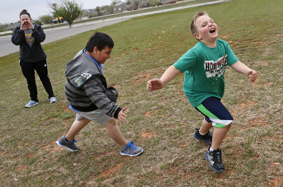 Photo - Jonthan Esparza, 9, chases Jaiden Pertree, 8, as Meg Jones watches during a game of scream tag at Kid's Maniac Fitness in Moore, Okla., Tuesday, April 9, 2013. Photo by Bryan Terry, The Oklahoman  Bryan Terry