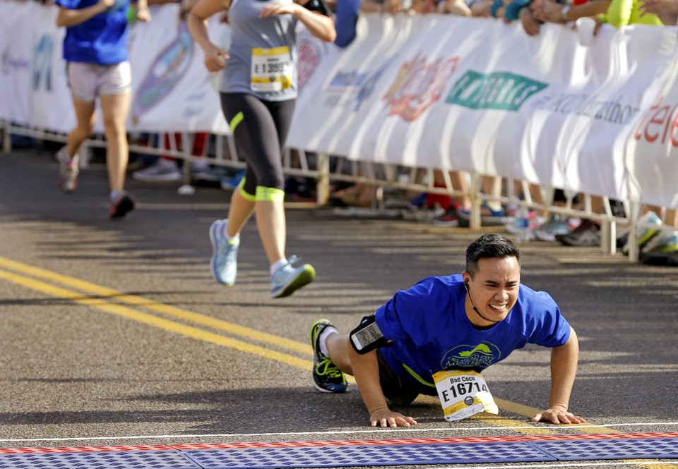 Photo - Benjamin Bacaoco stops to do a push up before crossing the finish line for the half marathon during the Oklahoma Memorial Marathon in Oklahoma City, Okla. on Sunday, April 24, 2016.   Photo by Chris Landsberger, The Oklahoman