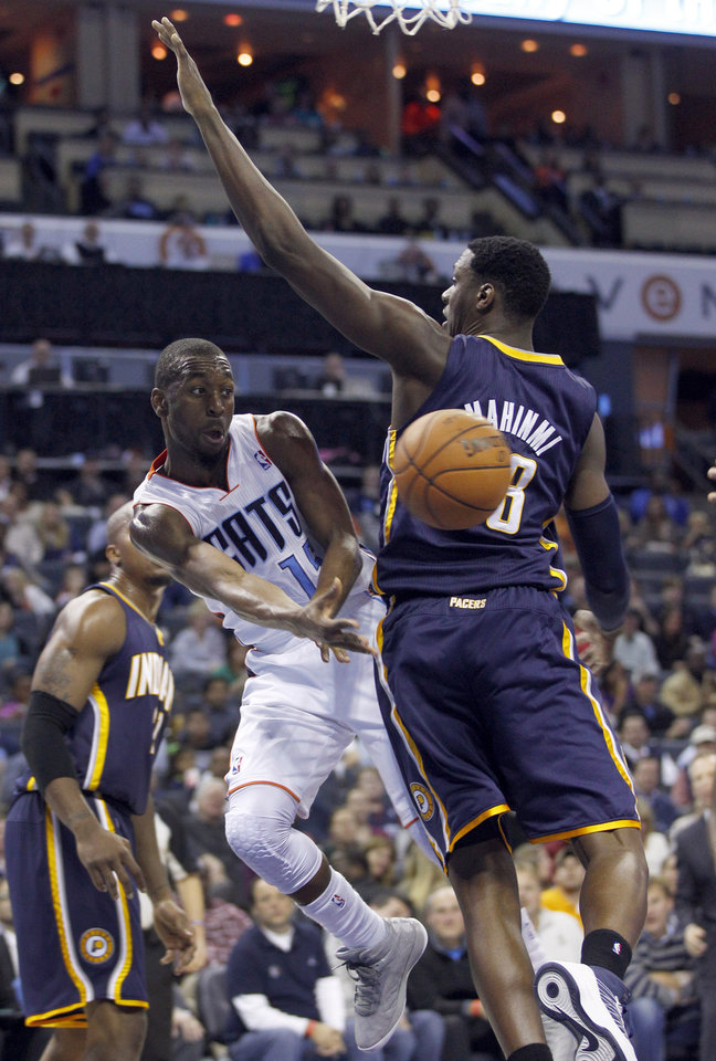 Charlotte Bobcats' Kemba Walker, left, passes the ball around Indiana Pacers' Ian Mahinmi, right, during the second half of an NBA basketball game in Charlotte, N.C., Friday, Nov. 2, 2012. The Bobcats won 90-89. (AP Photo/Chuck Burton)