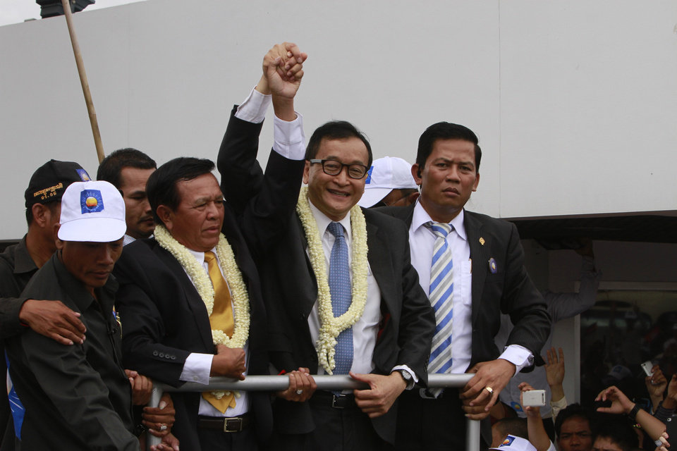 Photo - Sam Rainsy, center, president of Cambodia National Rescue Party (CNRP) holds hands with his party's Vice President Kem Sokha on his arrival at Phnom Penh International Airport, in Phnom Penh, Cambodia, Friday, July 19, 2013. Thousands of cheering supporters greeted Cambodian opposition leader Rainsy as he returned from self-imposed exile Friday to spearhead his party's election campaign against well-entrenched Prime Minister Hun Sen. (AP Photo/Heng Sinith)