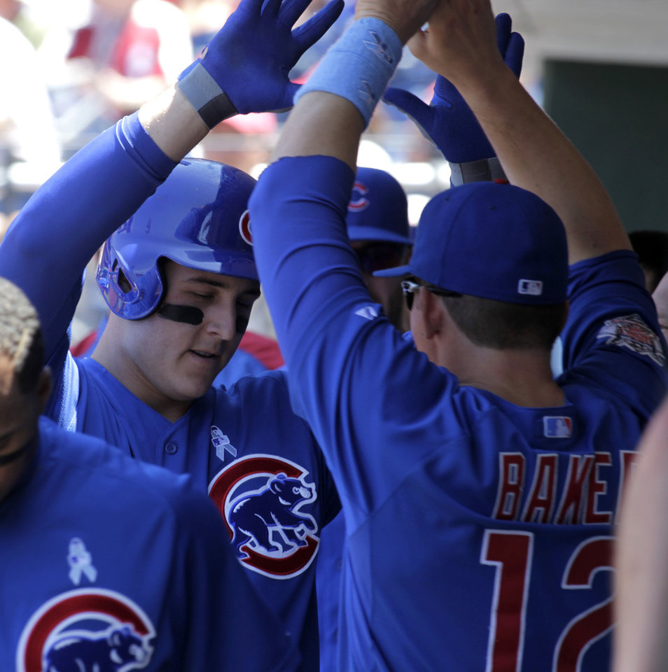 Photo - Chicago Cubs' Anthony Rizzo, left, celebrates with teammate John Baker (12) after hitting a solo home run against the  Philadelphia Phillies in the first inning of a baseball game on Sunday, June 15, 2014, in Philadelphia. (AP Photo/H. Rumph Jr)