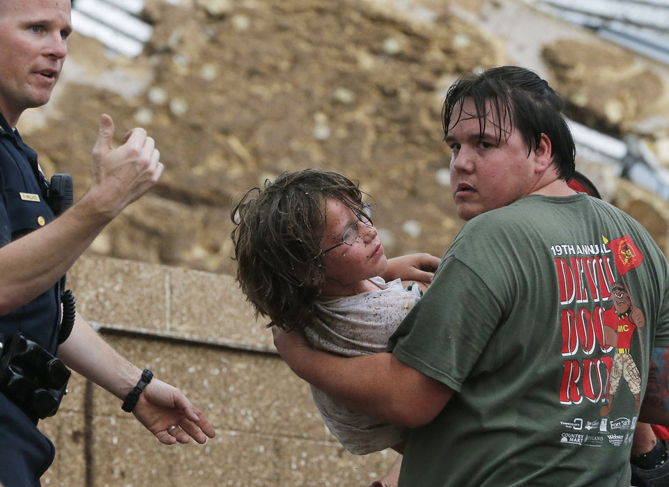 A child is carried from the rubble of the Plaza Towers Elementary School following a tornado in Moore, Okla., Monday, May 20, 2013. A tornado as much as a mile (1.6 kilometers) wide with winds up to 200 mph (320 kph) roared through the Oklahoma City suburbs Monday, flattening entire neighborhoods, setting buildings on fire and landing a direct blow on an elementary school. (AP Photo/Sue Ogrocki) ORG XMIT: OKSO126
