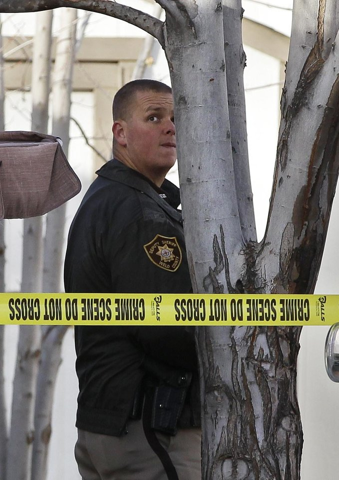 "A police officer works at the scene of an apparent murder-suicide, which officials say left four dead inside a home, according to officials, in Longmont, Colo., Tuesday Dec. 18, 2012. Weld County sheriff's spokesman Tim Schwartz says dispatchers heard the woman who called 911 scream ""No, no, no,"" and then they heard a gunshot. Schwartz says a man grabbed the phone and said he was going to kill himself, and dispatchers heard another shot.  (AP Photo/Brennan Linsley)"