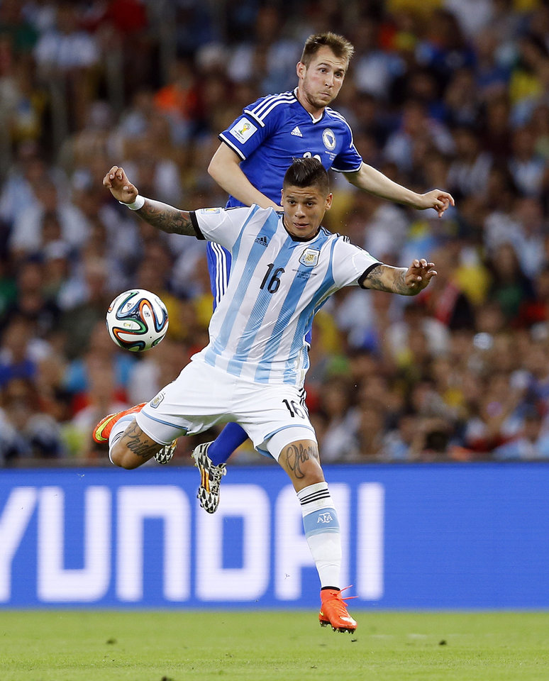 Photo - Argentina's Marcos Rojo (16) gets ahead of Bosnia's Izet Hajrovic to stop the ball during their group F World Cup soccer match at the Maracana Stadium in Rio de Janeiro, Brazil, Sunday, June 15, 2014.  (AP Photo/Kirsty Wigglesworth)