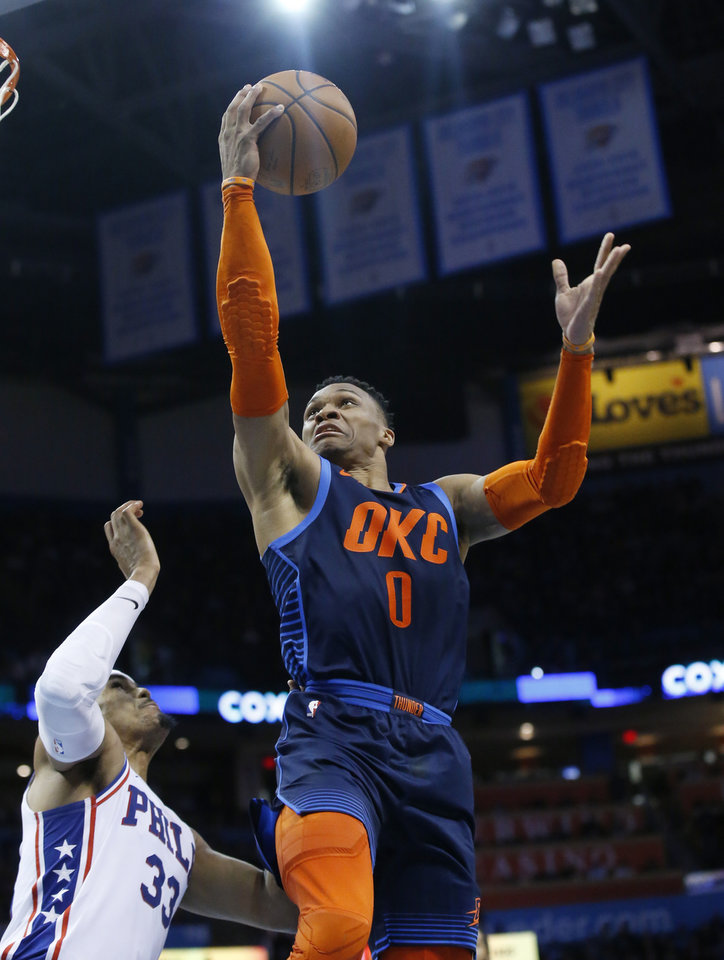 Photo - Oklahoma City Thunder guard Russell Westbrook (0) goes to the basket in front of Philadelphia 76ers forward Tobias Harris, left, during the second half of an NBA basketball game Thursday, Feb. 28, 2019, in Oklahoma City. (AP Photo/Sue Ogrocki)
