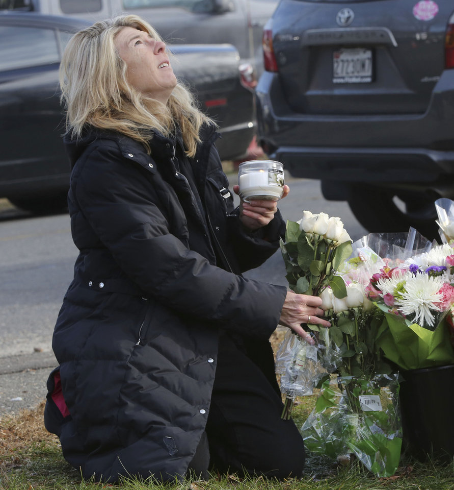 Andrea Jeager, of Hesperus, Colo., says a prayer as she places flowers and a candle at a makeshift memorial at a sign for the Sandy Hook school, Saturday, Dec. 15, 2012 in Sandy Hook village of Newtown, Conn. The massacre of 26 children and adults at Sandy Hook Elementary school elicited horror and soul-searching around the world even as it raised more basic questions about why the gunman, 20-year-old Adam Lanza, would have been driven to such a crime and how he chose his victims. (AP Photo/Mary Altaffer) ORG XMIT: CTMA109