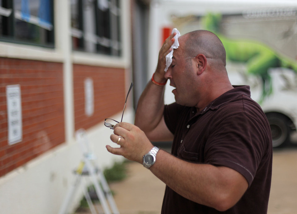 Photo - OKLAHOMA CITY THUNDER / NBA FINALS / NBA BASKETBALL / SUPPORT / MIAMI HEAT:  Daniel Cochran, an employee at The Brace Place, takes a break from painting windows outside of his office building to wipe sweat from his face in Oklahoma City, Monday, June 11, 2012.  Photo by Garett Fisbeck, The Oklahoman