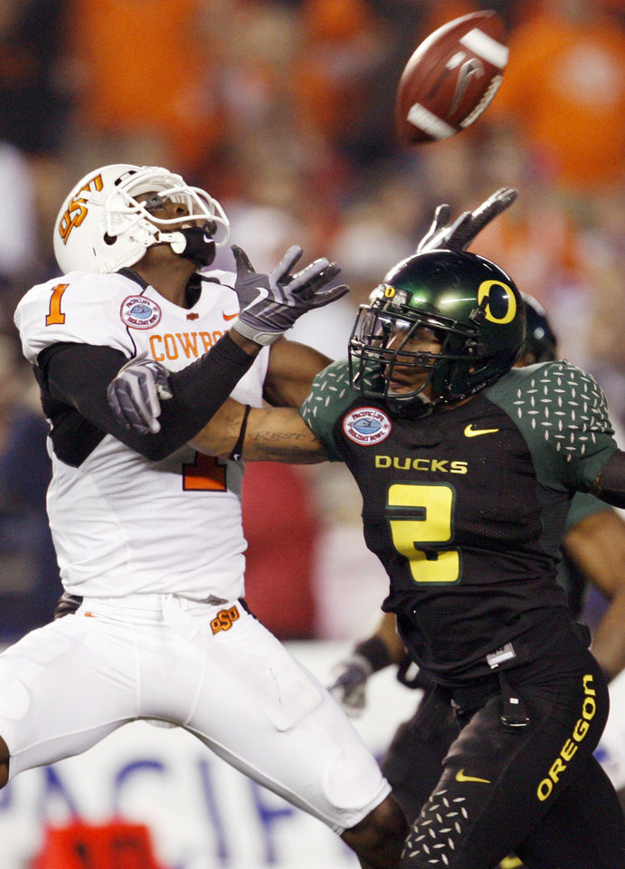 Photo - Oregon's T.J. Ward (2) has a hand on OSU's Dez Bryant (1) as Bryant attempts to pull in a pass in the second quarter of the Holiday Bowl college football game between Oklahoma State and Oregon at Qualcomm Stadium in San Diego, Tuesday, Dec. 30, 2008. The pass was incomplete. PHOTO BY NATE BILLINGS, THE OKLAHOMAN