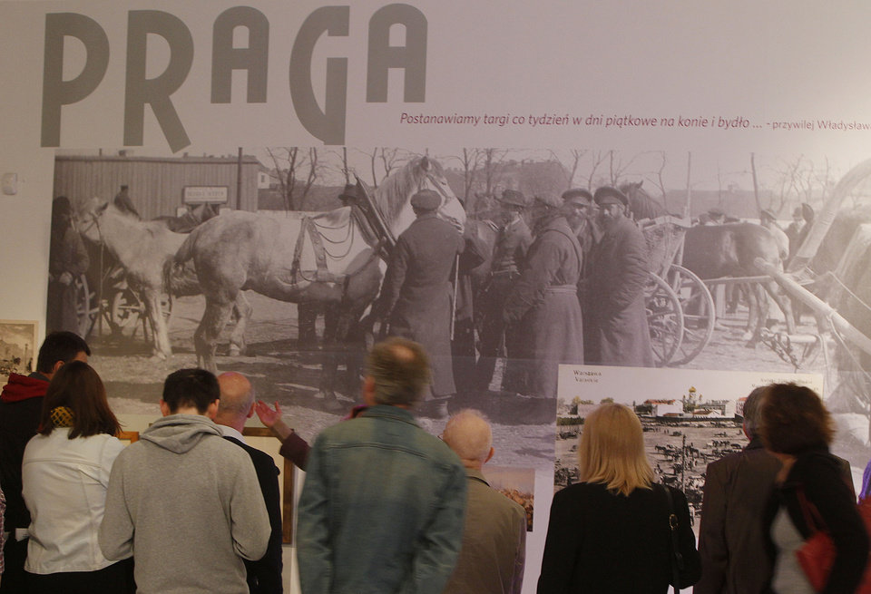 Photo - People watch a picture of the horse market in pre-World War II Warsaw's Praga district, at a new exhibition by the Museum of the History of Polish Jews, in Warsaw, Poland, on Thursday, March 27, 2014. The exhibition that will run through June 30 documents Jewish life in Warsaw before the Holocaust. (AP Photo/Czarek Sokolowski)