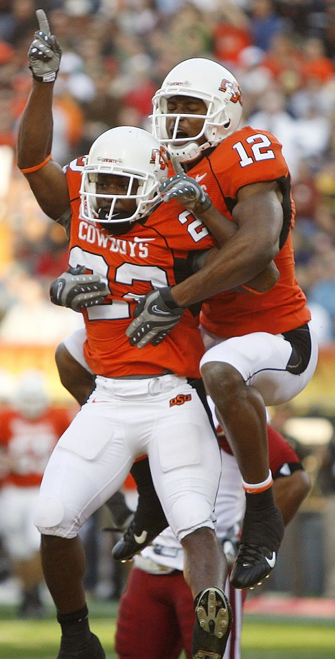 Photo - Oklahoma State's Adarius Bowman (12) and Dantrell Savage (22) celebrate after Savage's touchdown in the first half during the Insight Bowl college football game between Oklahoma State University (OSU) and the Indiana University Hoosiers (IU) at Sun Devil Stadium on Monday, Dec. 31, 2007, in Tempe, Ariz. 