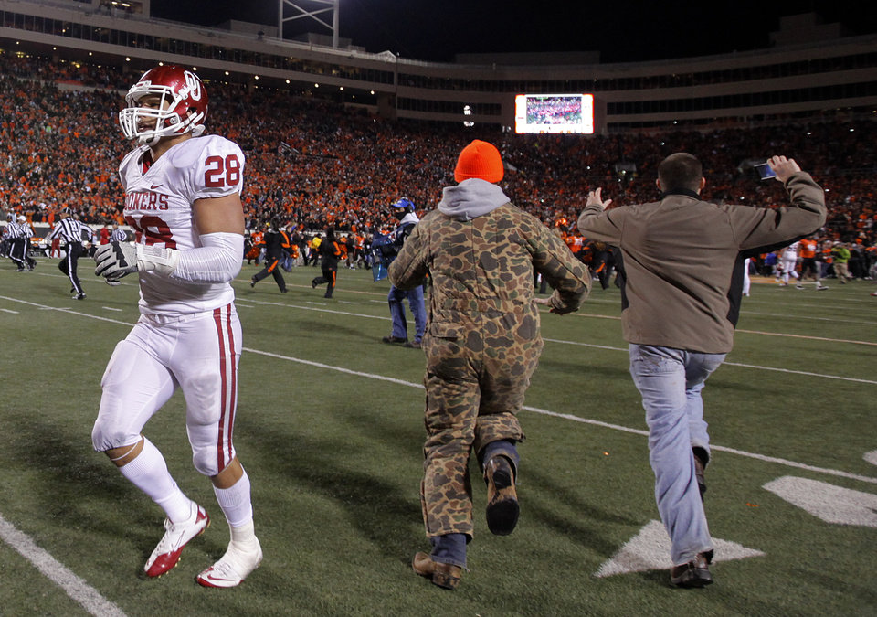 Photo - Oklahoma's Travis Lewis (28) runs off the field as Cowboy fans run onto the field after OSU's 44-10 win over Oklahoma during the Bedlam college football game between the Oklahoma State University Cowboys (OSU) and the University of Oklahoma Sooners (OU) at Boone Pickens Stadium in Stillwater, Okla., Saturday, Dec. 3, 2011. Photo by Chris Landsberger, The Oklahoman