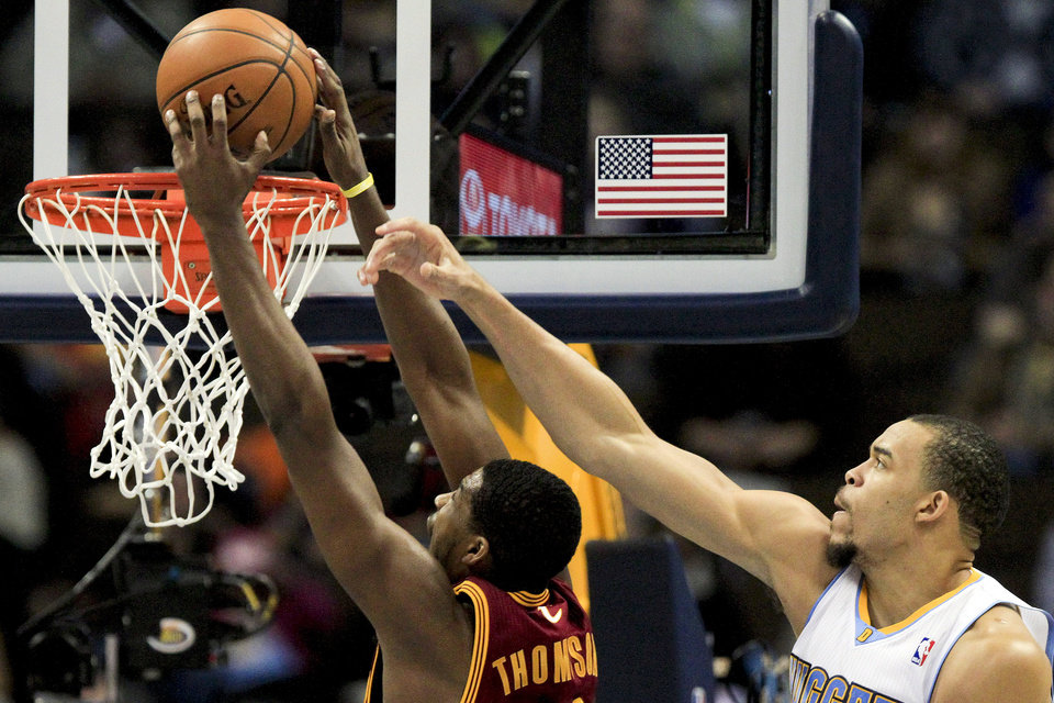 Cleveland Cavaliers power forward Tristan Thompson, left, scores past Denver Nuggets'  JaVale McGee, right, during the first quarter of an NBA basketball game Friday, Jan. 11, 2013, in Denver. (AP Photo/Barry Gutierrez)