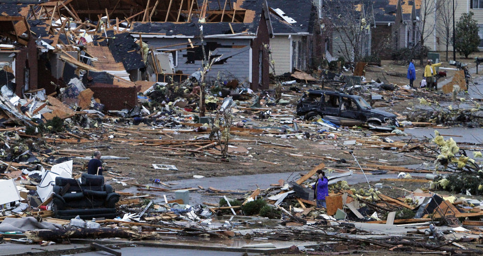 FILE - In this Jan. 23, 2012, file photo, residents walk around through the debris of their neighborhood after a tornado ripped through the Trussville, Ala. area. Storm chasers are watching the Southeast as a nasty storm brews with the potential to spin off a batch of tornadoes. Tornado season is just about here and forecasters believe twisters are possible Thursday and Friday. But in reality, it got an early and deadly start in late January when two people were killed by separate twisters in Alabama. The season usually starts in March and then ramps up for the next couple of months, but forecasting tornado seasons is even more imprecise than predicting hurricane seasons. (AP Photo/Butch Dill) ORG XMIT: WX101