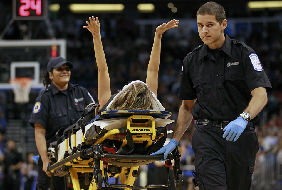 Jamie Woode, a former college cheerleader and Magic Stunt Team member, fell during a routine and is wheeled off the floor on a stretcher as she waves her arms to fans during the first half of an NBA basketball game between the Orlando Magic and the New York Knicks, Tuesday, Nov. 13, 2012, in Orlando, Fla. She was transferred to a nearby hospital. (AP Photo/John Raoux)