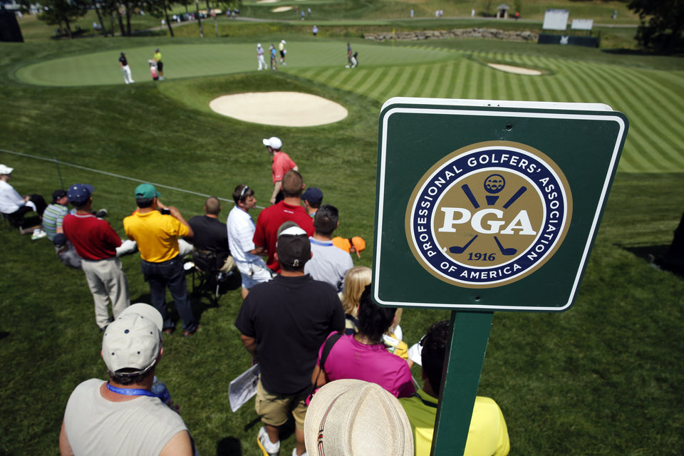 Photo - A few fans watch as golfers putt on the 16th green during a practice round at the PGA Championship golf tournament at Valhalla Golf Club Monday, Aug. 4, 2014, in Louisville, Ky. The tournament starts on Thursday. (AP Photo/Jeff Roberson)